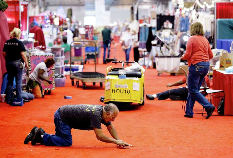 Isador Gomez makes some last-minute adjustments to the carpet before the 33rd annual Nutcracker Market at Reliant Center Wednesday, Nov. 6, 2013, in Houston. Photo: Johnny Hanson, Houston Chronicle / Houston Chronicle