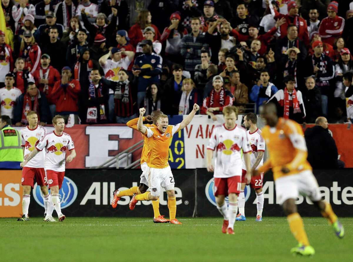Houston Dynamo midfielder Andrew Driver, center, celebrates a goal by teammate forward Omar Cummings, back, in overtime during an MLS soccer playoff game against the New York Red Bulls, Wednesday, Nov. 6, 2013, in Harrison, N.J. (AP Photo/Julio Cortez)