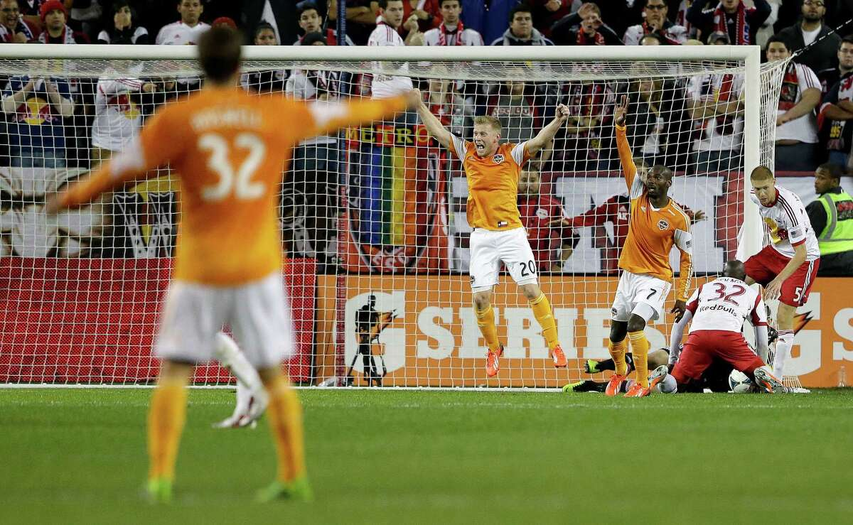 Houston Dynamo forward Omar Cummings (7) celebrates with teammate midfielder Andrew Driver (20) after Cummings scored a goal against the New York Red Bulls in overtime during an MLS soccer playoff game Wednesday, Nov. 6, 2013, in Harrison, N.J. (AP Photo/Julio Cortez)