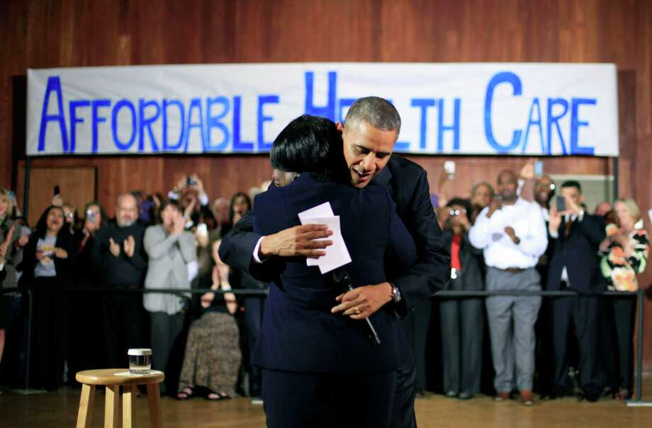 President Barack Obama hugs Edna Pemberton, who introduced him Wednesday at Temple Emanu-El in Dallas, before speaking with volunteers who help people enroll through the HealthCare.gov site. Photo: Pablo Martinez Monsivais, STF / AP