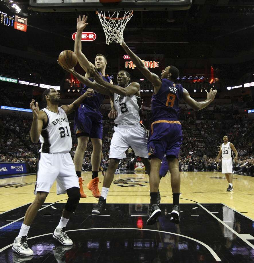 Spurs' Kawhi Leonard (02) drives to the basket against Phoenix Suns' Miles Plumlee (22) and Channing Frye (08) at the AT&T Center on Wednesday, Nov. 6, 2013. (Kin Man Hui/San Antonio Express-News) Photo: Kin Man Hui, San Antonio Express-News