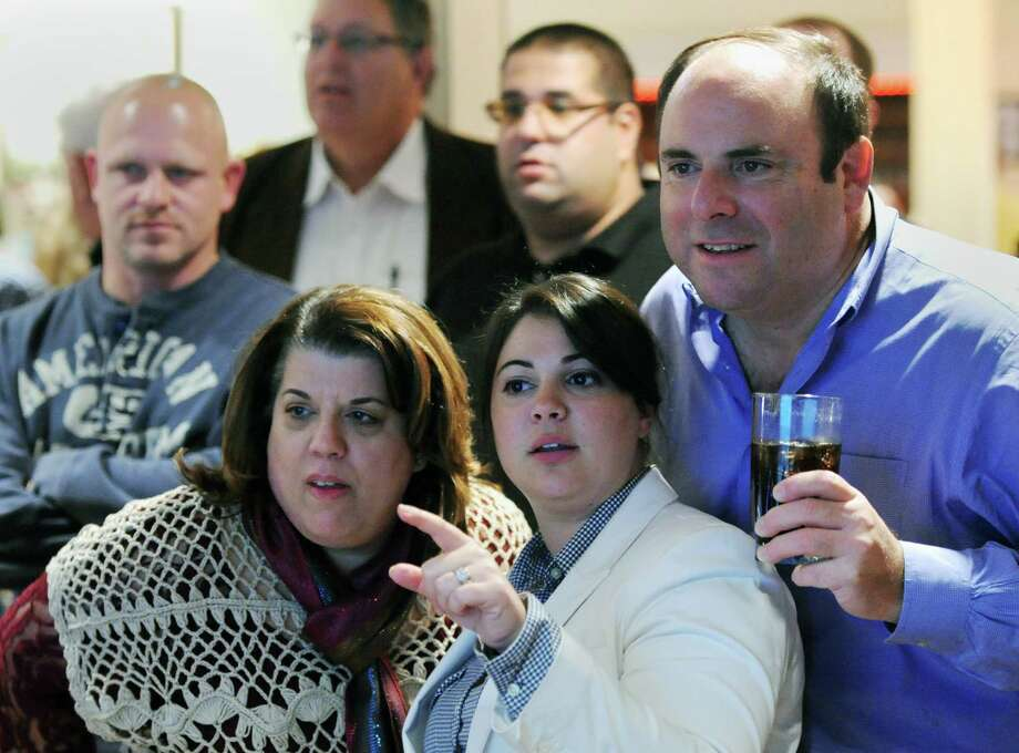 People gather around a screen to watch as the municipal election results come in at the Amerigo Vespucci Lodge in Danbury on Tuesday. Photo: Tyler Sizemore / The News-Times