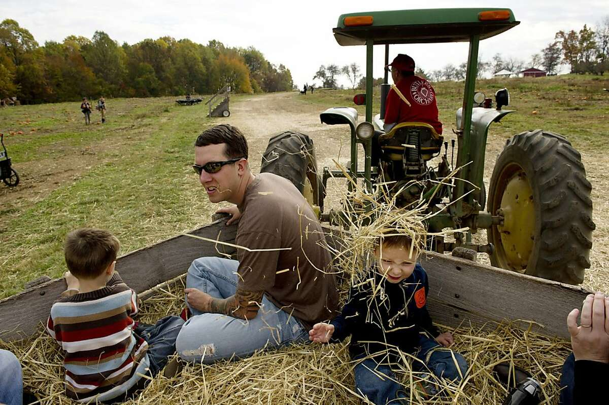 In this Oct. 30, 2013 photo, Drew Lidster, second from left, takes part in a hay ride with his sons, Ayden Lidster, 5, left, and Micah Lidster, 3, as Danny Stinson, top right, drives the tractor pulling the wagon at Butler's Orchard, in Germantown, MD. Hay rides are one place patrons often lose items which are collected and logged electronically. (AP Photo/The Washington Post, Matt McClain)