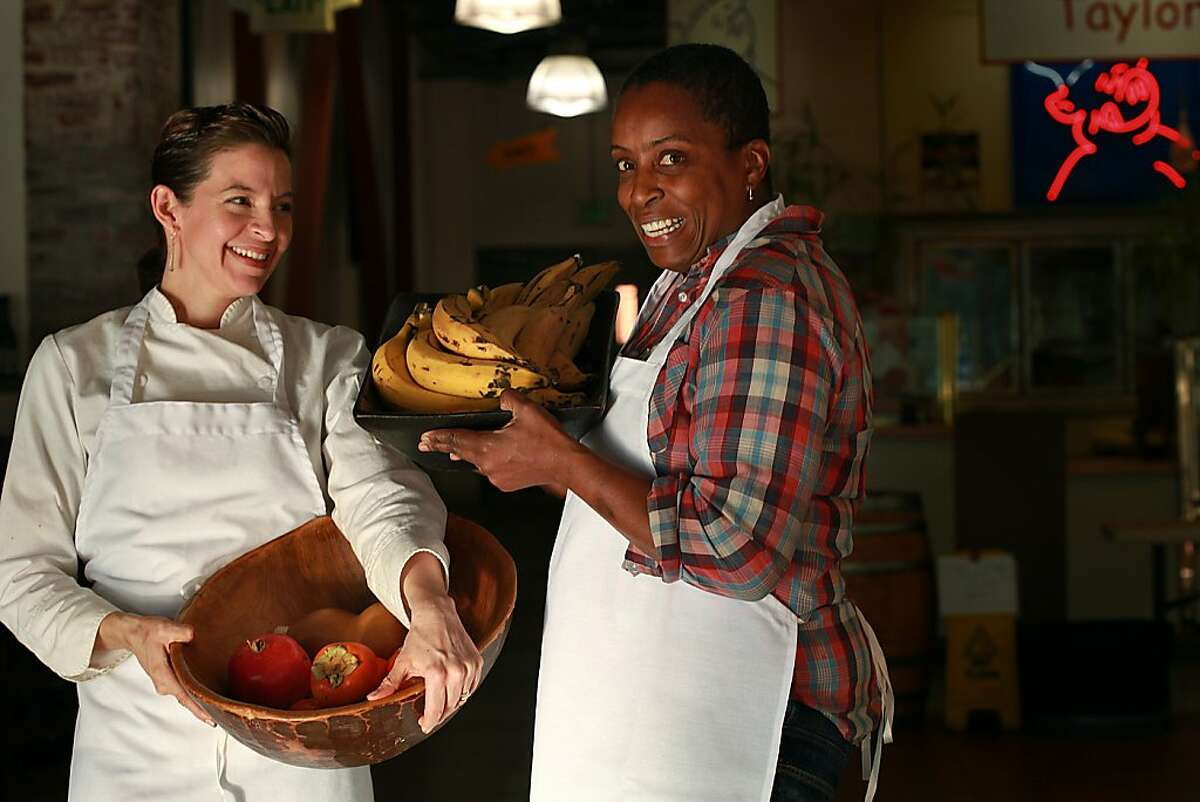 Chefs Dominica Rice (left) of Cosecha and Sarah Kirnon (right) of Miss Ollie's carry fruits inside of Old Oakland's historic Swan Market in downtown Oakland, California, on Thursday, October 31, 2013.