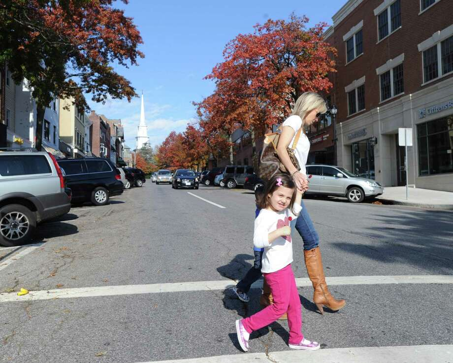 A woman and child cross Greenwich Avenue in Greenwich on Saturday. Photo: Bob Luckey / Greenwich Time