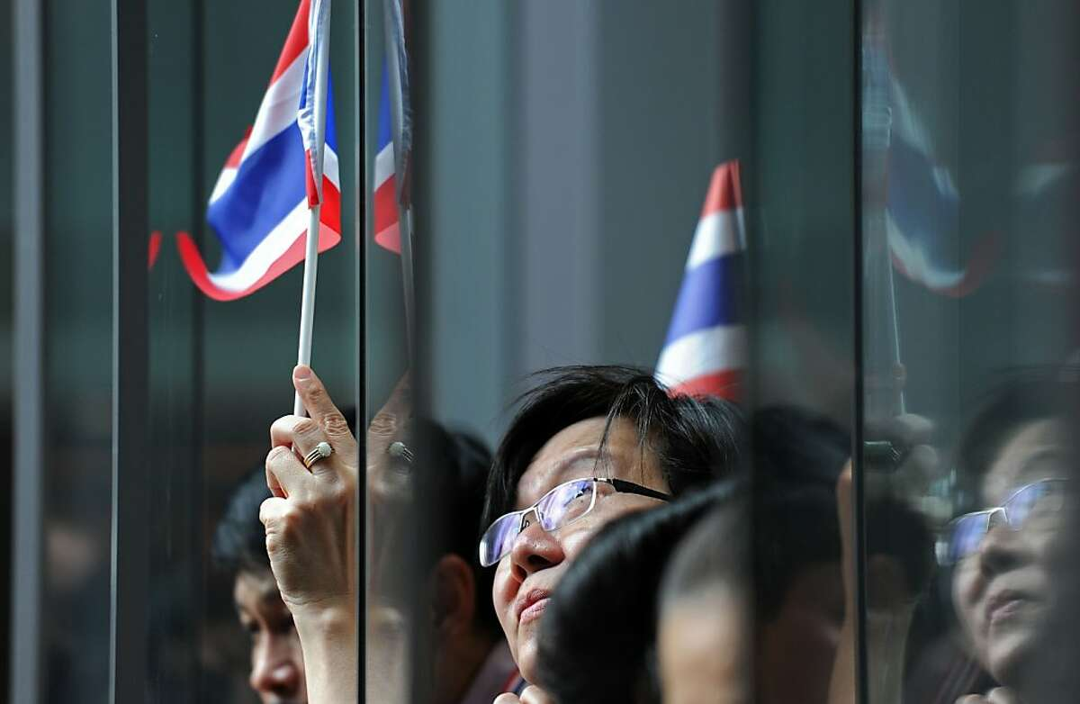 Thai opposition protesters wave national flags during a rally against a controversial political amnesty bill that has sparked mass anti-government protests, urging the country to
