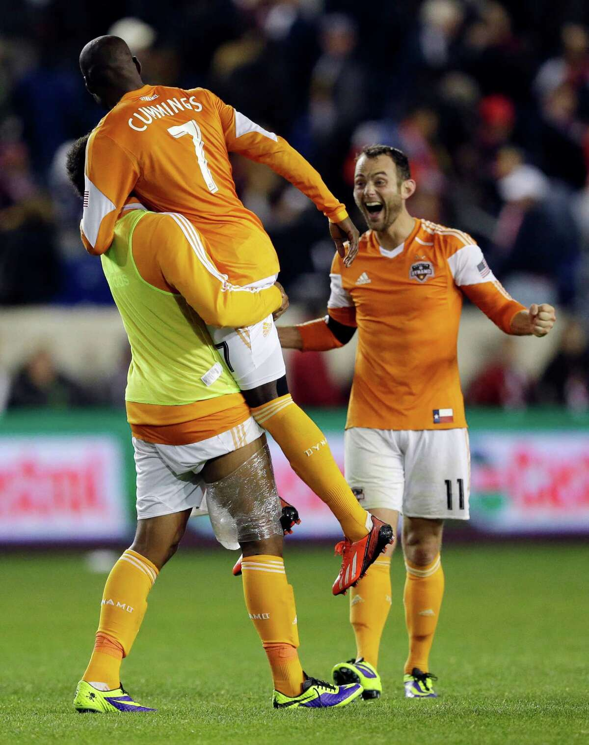 After scoring the winning goal in extra time, Omar Cummings (7) gets a lift from Giles Barnes to the delight of Brad Davis, right.