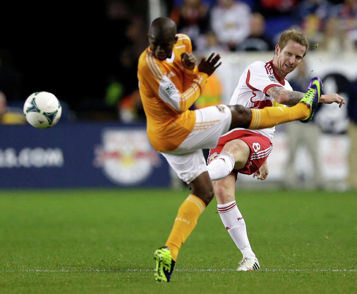 New York Red Bulls' David Carney, right, kicks the ball as Houston Dynamo defender Kofi Sarkodie defends against him during the first half of an MLS soccer playoff game Wednesday, Nov. 6, 2013, in Harrison, N.J. (AP Photo/Julio Cortez)