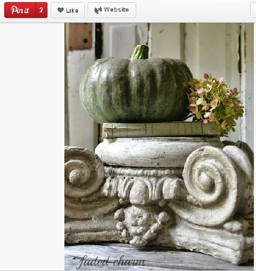 I adore how the green from the pumpkin complements the green tones in the capital statuary, giving the vignette an elegant, antique look. Photo: Screengrab From Pinterest.com