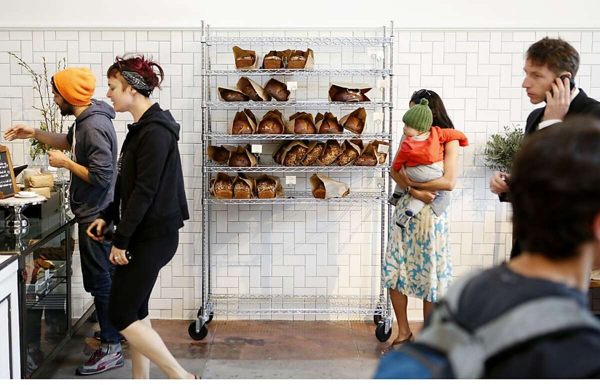 A rack of bread stands next to customers at the new bakery and coffee bar The Mill at 736 Divisadero on Tuesday, March 12, 2013 in San Francisco, Calif.