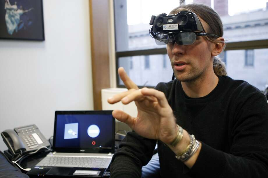 Caleb Garling of the Chronicle demos the i-Touch-in-Air wearable computer system. The red dot on the computer screen is where his fingertip is on the same images in the lenses. Photo: Michael Short, The Chronicle
