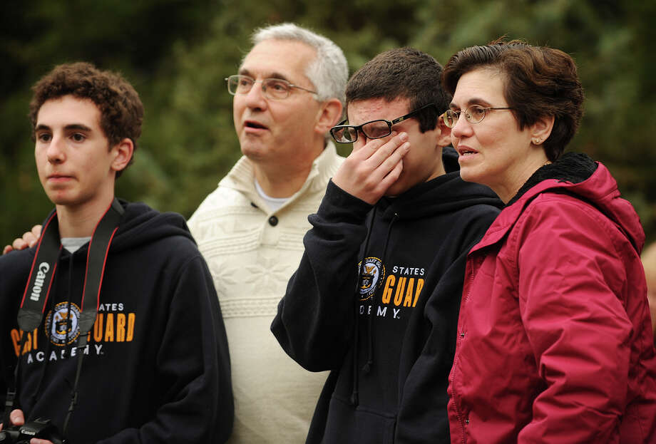 The Vargoshe family looks on and 12-year-old Noah Vargoshe sheds a tear as the new Rockefeller Center Christmas tree, a 76-foot tall Norway spruce, is cut down from their property at 15 Kazo Drive in Shelton, Connecticut on Thursday, November 7, 2013. From left are Nathan, 15, John, Noah, and Louise Vargoshe. Photo: Brian A. Pounds / Connecticut Post