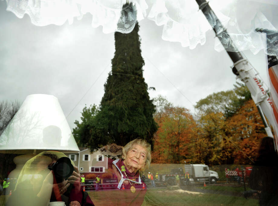 95-year-old Eleanor Vargoshe watches through the bay window of the Vargoshe home as the new Rockefeller Center Christmas tree, a 76-foot tall Norway spruce, is removed from the home's front yard at 15 Kazo Drive in Shelton, Connecticut on Thursday, November 7, 2013. Photo: Brian A. Pounds / Connecticut Post