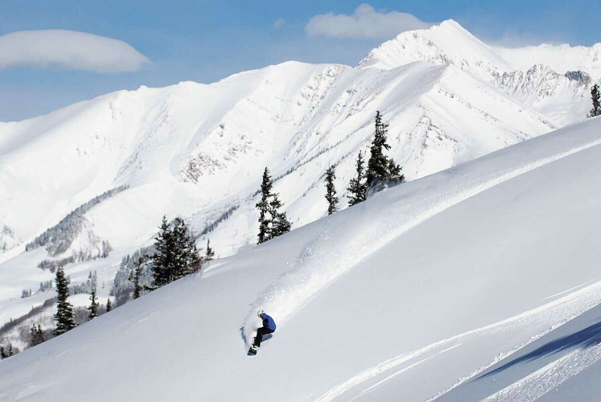 A snowboarder cuts across fresh powder at Crested Butte Mountain Resort.