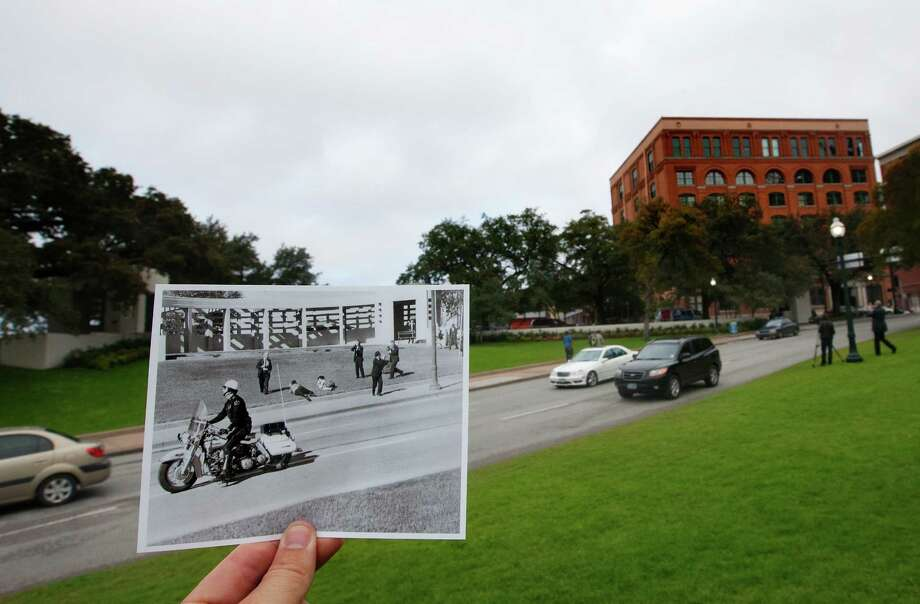A November 22, 1963 photo by Dallas Morning News photographer Tom Dillard showing spectators lying on the ground in Dealey Plaza as a motorcycle police officer drives by immediately after the shooting of President John F. Kennedy is juxtaposed outside of the current day Elm Street, Tuesday, Nov. 5, 2013, in Dallas. Photo: Cody Duty, Houston Chronicle / © 2013 Houston Chronicle