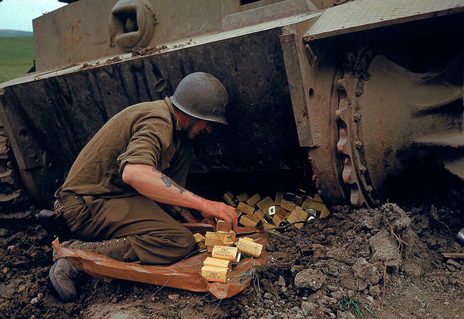 A US Army Corps of Engineers solider packs 1/2 pound tins of the explosive TNT under one end of an abandoned German tank in preparation for detonation during military operations in the El Guettar Valley, Tunisia, early 1943. Photo: Eliot Elisofon., Time & Life Pictures/Getty Image / Time & Life Pictures