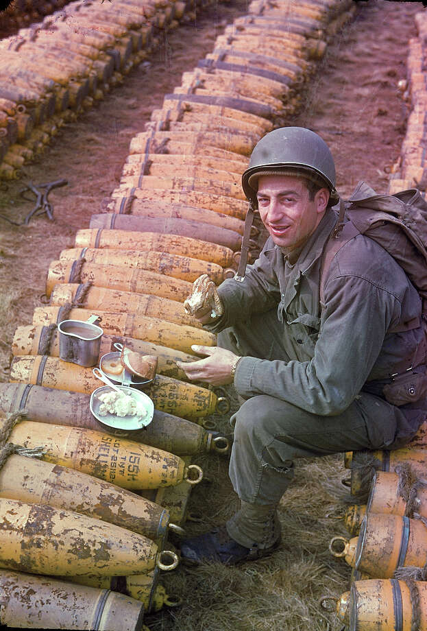 An unidentified American soldier sits and eats his meal (which includes chicken, mashed potatoes, bread, and pineapple) atop rows of a stockpiled ammunition shells, England, May 1944. Photo: Frank Scherschel, Time & Life Pictures/Getty Image / Time & Life Pictures