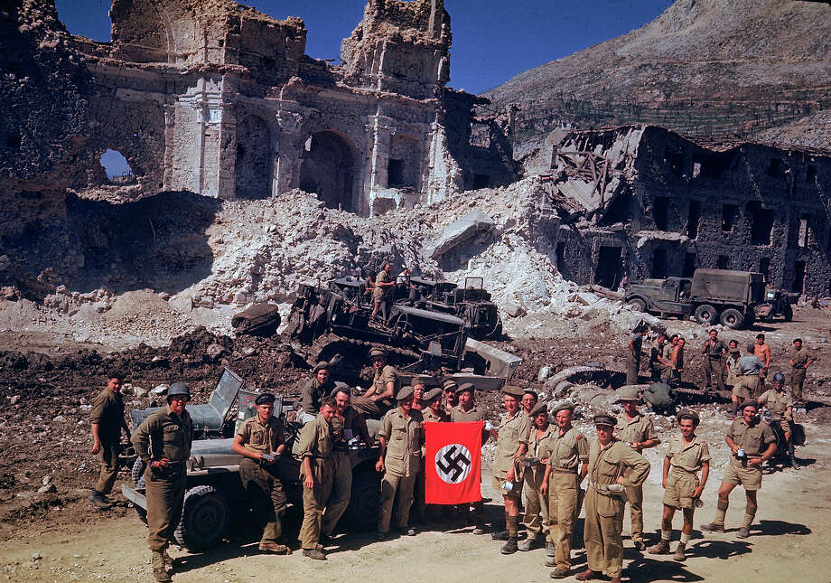 British and South African soldiers hold up Nazi trophy flag while combat engineers on bulldozers clear a path through the debris of the bombed out city of Cassino in 1943. Photo: Carl Mydans, Time & Life Pictures/Getty Image / Time & Life Pictures