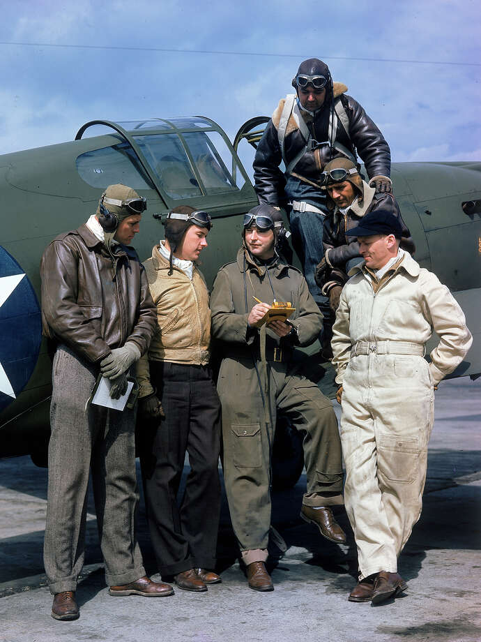 Curtiss Wright's chief test pilot H. Lloyd Child (center) writes on a clipboard as he stands with other pilots on a tarmac near the companies manufacturing plant, Buffalo, New York, 1941. Photo: Dmitri Kessel, Time & Life Pictures/Getty Image / Time & Life Pictures
