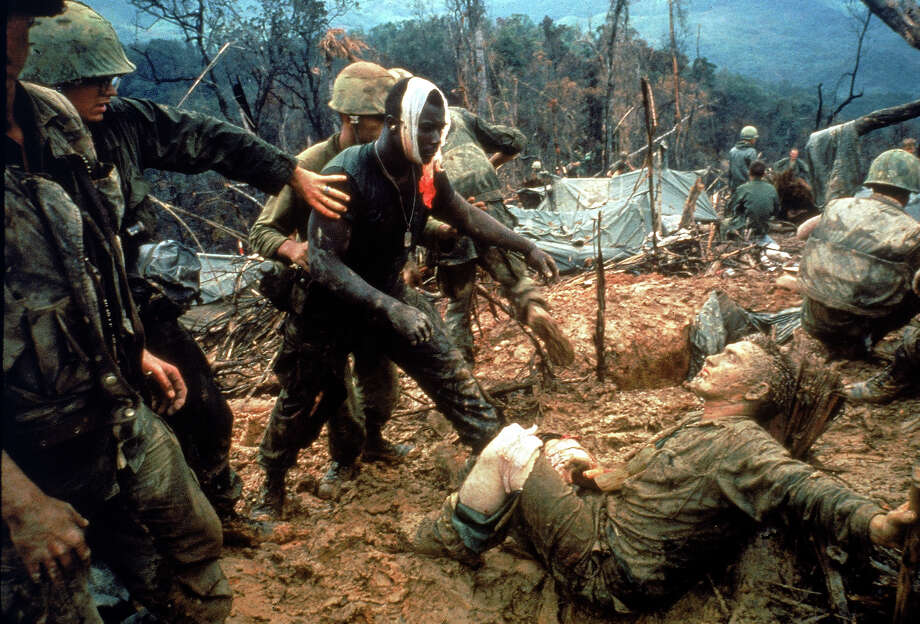 Wounded Marine Gunnery Sargeant Jeremiah Purdie (C) is led past stricken comrades after fierce firefight for control of Hill 484, south of DMZ in South Vietnam, 1966. Photo: Larry Burrows, Time & Life Pictures/Getty Image / Time Life Pictures