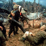 Wounded Marine Gunnery Sargeant Jeremiah Purdie (C) is led past stricken comrades after fierce firefight for control of Hill 484, south of DMZ in South Vietnam, 1966.