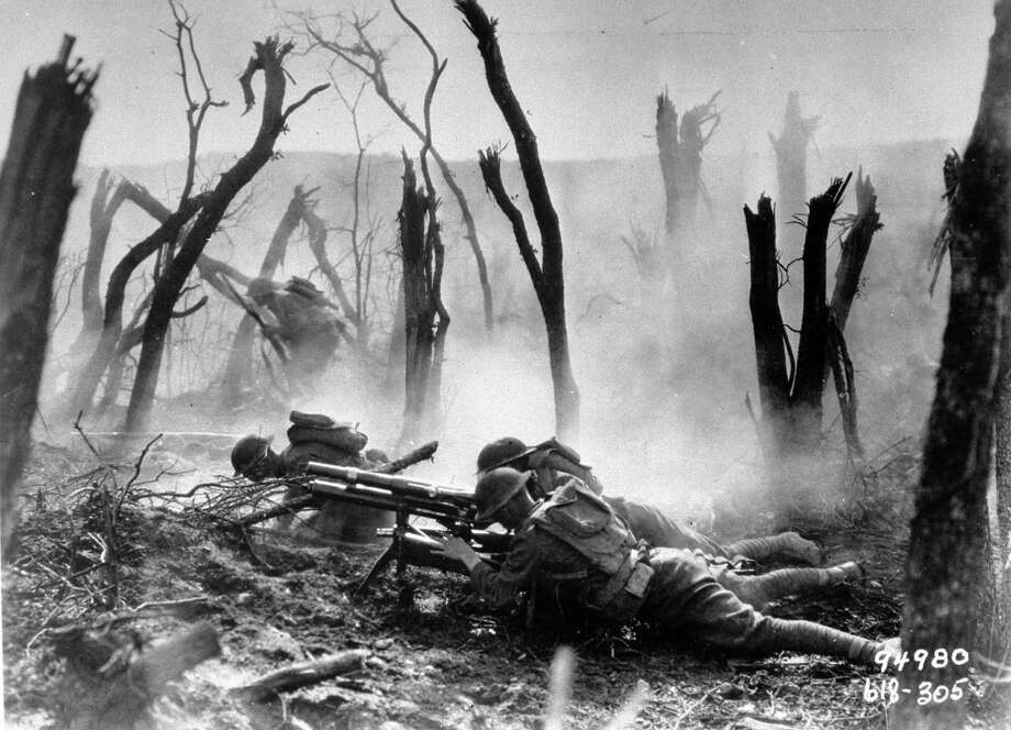 A gun crew from Regimental HQ Co., 23rd Infantry, lying on ground atop branches from bombed-out trees & firing 37-mm gun during advance against German entrance position during WWI, 1918. Photo: Time Life Pictures, Time & Life Pictures/Getty Image / Time Life Pictures