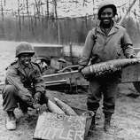 African American soldiers posing in the fields with ammunition shells with the inscription reading Happy Easter Hitler, 1945.