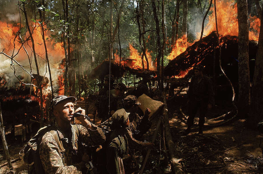 US Army Special Forces Capt. Vernon Gillespie contacting his base camp by radio while Vietnamese soldiers burn down a Vietcong hideout, 1964. Photo: Larry Burrows, Time & Life Pictures/Getty Image / Time Life Pictures