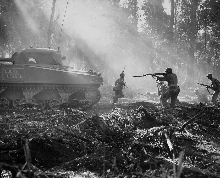 American soldiers using a Sherman tank for cover as it and they advance on Japanese positions during the fight to take Bougainville, 1944. Photo: Time Life Pictures, Time & Life Pictures/Getty Image / Time Life Pictures
