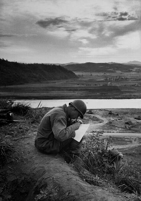 American soldier writing a letter home while sitting on a mound near his front line bunker on a battle free Sunday, 1951. Photo: Joseph Scherschel, Time & Life Pictures/Getty Image / Time & Life Pictures