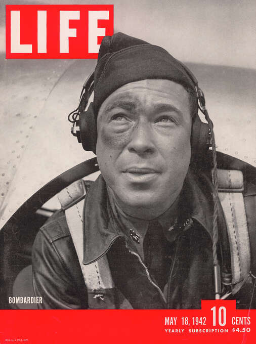The cover of Life magazine features a close-up of a bombadier-in-training as he leans out of an airplane at an Air Force flight school, May 18, 1942. He wears a leather jacket, a cap, and headphones, as well as sporting what appears to be a black eye. Photo: William C. Shrout., Time & Life Pictures/Getty Image / Time Life Pictures