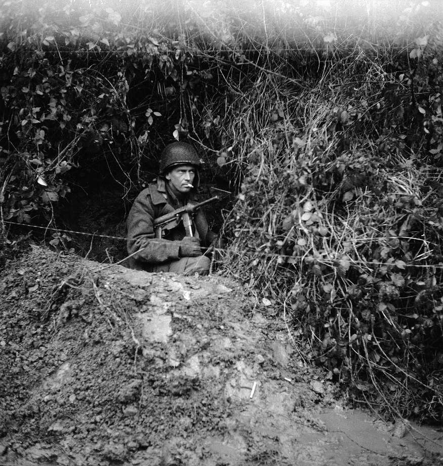 An American soldier sits in a foxhole and grimly smokes a cigarette during a break in World War II combat, Germany, 1944. He holds an M3 submachine gun under his arm. Photo: John Florea., Time & Life Pictures/Getty Image / Time Life Pictures