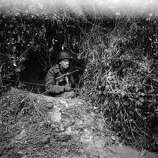 An American soldier sits in a foxhole and grimly smokes a cigarette during a break in World War II combat, Germany, 1944. He holds an M3 submachine gun under his arm.