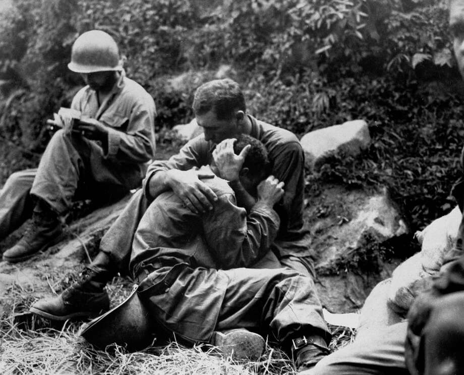Grief-stricken American infantryman whose buddy has just been killed is comforted by a comrade while corpsman in background. methodically fills out casualty tags during a lull in the fighting somewhere near Haktong-ni, 1950. Photo: Sfc. Al Chang, Time & Life Pictures/Getty Image / Time & Life Pictures