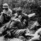 Grief-stricken American infantryman whose buddy has just been killed is comforted by a comrade while corpsman in background. methodically fills out casualty tags during a lull in the fighting somewhere near Haktong-ni, 1950.