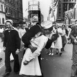 A jubilant American sailor clutching a white-uniformed nurse in a back-bending, passionate kiss as he vents his joy while thousands jam Times Square to celebrate the long awaited-victory over Japan, 1945.