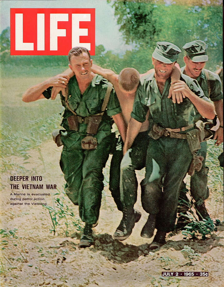 The cover of Life magazine shows a pair of American soldiers as they carry a wounded comrade to safety, accompanied by the headline 'Deeper into the Vietnam War,' Vietnam, July 2, 1965. Photo: Bill Eppridge, Time & Life Pictures/Getty Image / Time & Life Pictures