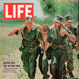 The cover of Life magazine shows a pair of American soldiers as they carry a wounded comrade to safety, accompanied by the headline 'Deeper into the Vietnam War,' Vietnam, July 2, 1965.