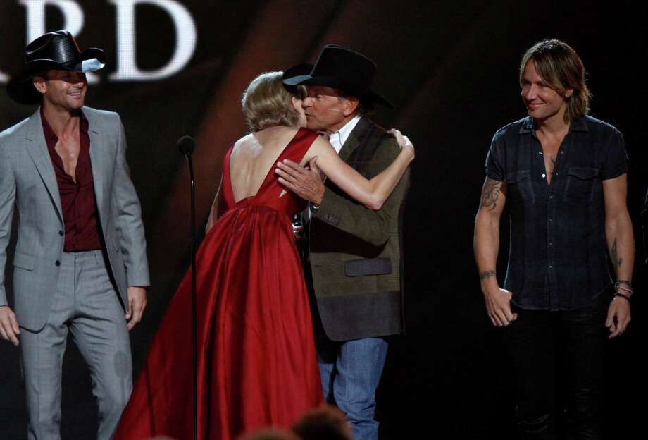 Taylor Swift, second left, is congratulated by presenter George Strait as she accepts the Pinnacle award at the 47th annual CMA Awards at Bridgestone Arena on Wednesday, Nov. 6, 2013, in Nashville, Tenn.  Looking on at left is presenter Tim McGraw and at right Keith Urban. (Photo by Wade Payne/Invision/AP) ORG XMIT: TNDC274 Photo: Wade Payne, AP / Invision