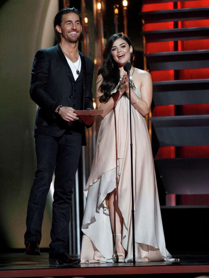 Presenters Jake Owen, left, and Lucy Hale speak on stage at the 47th annual CMA Awards at Bridgestone Arena on Wednesday, Nov. 6, 2013, in Nashville, Tenn. (Photo by Wade Payne/Invision/AP) ORG XMIT: TNPM112 Photo: Wade Payne, AP / Invision