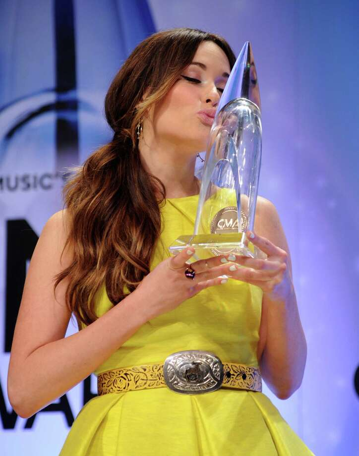 Kacey Musgraves kisses her award for new artist of the year backstage at the 47th annual CMA Awards at Bridgestone Arena on Wednesday, Nov. 6, 2013, in Nashville, Tenn. (Photo by Evan Agostini/Invision/AP) ORG XMIT: TNPM122 Photo: Evan Agostini, AP / Invision