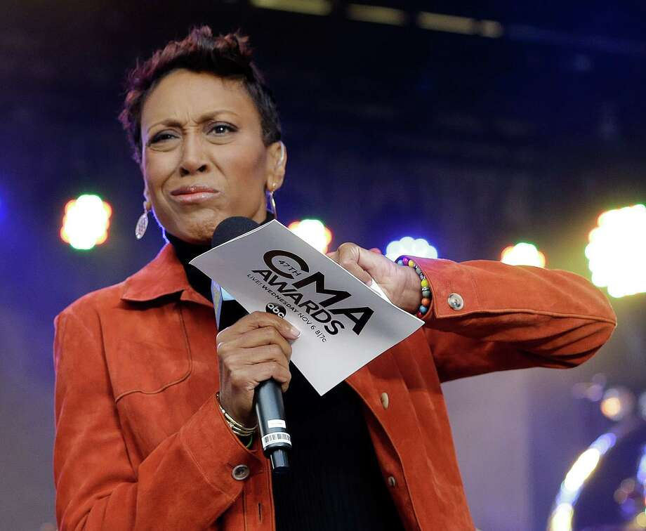 "Robin Roberts of the TV show ""Good Morning America"" struggles to open the envelope to read the winner of the Country Music Association music video of the year award, one of two awards announced during a broadcast from outside of Bridgestone Arena on Wednesday, Nov. 6, 2013, in Nashville, Tenn. The video for the song ""Highway Don't Care,"" by Tim McGraw and Taylor Swift, won the award. The CMA Awards will be held at the venue Wednesday night. (AP Photo/Mark Humphrey) ORG XMIT: TNMH107 Photo: Mark Humphrey, AP / AP"