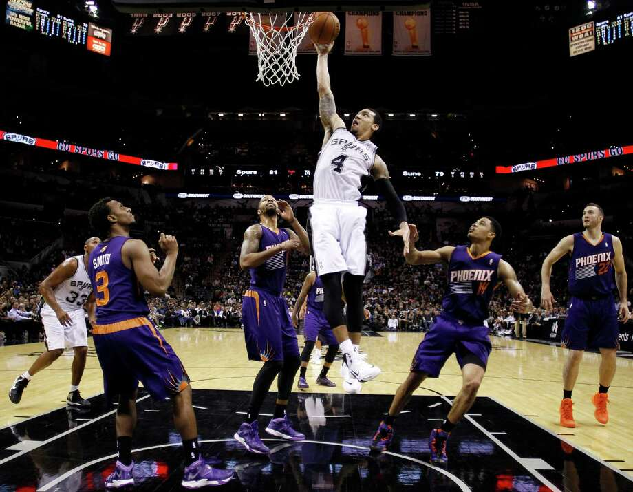 San Antonio Spurs' Danny Green (4) scores over Phoenix Suns defenders Ish Smith (3), Markieff Morris, Gerald Green (14) and Miles Plumlee (22) during the second half of an NBA basketball game Wednesday, Nov. 6, 2013, in San Antonio. San Antonio won 99-96. (AP Photo/Eric Gay) Photo: Eric Gay, Associated Press / AP