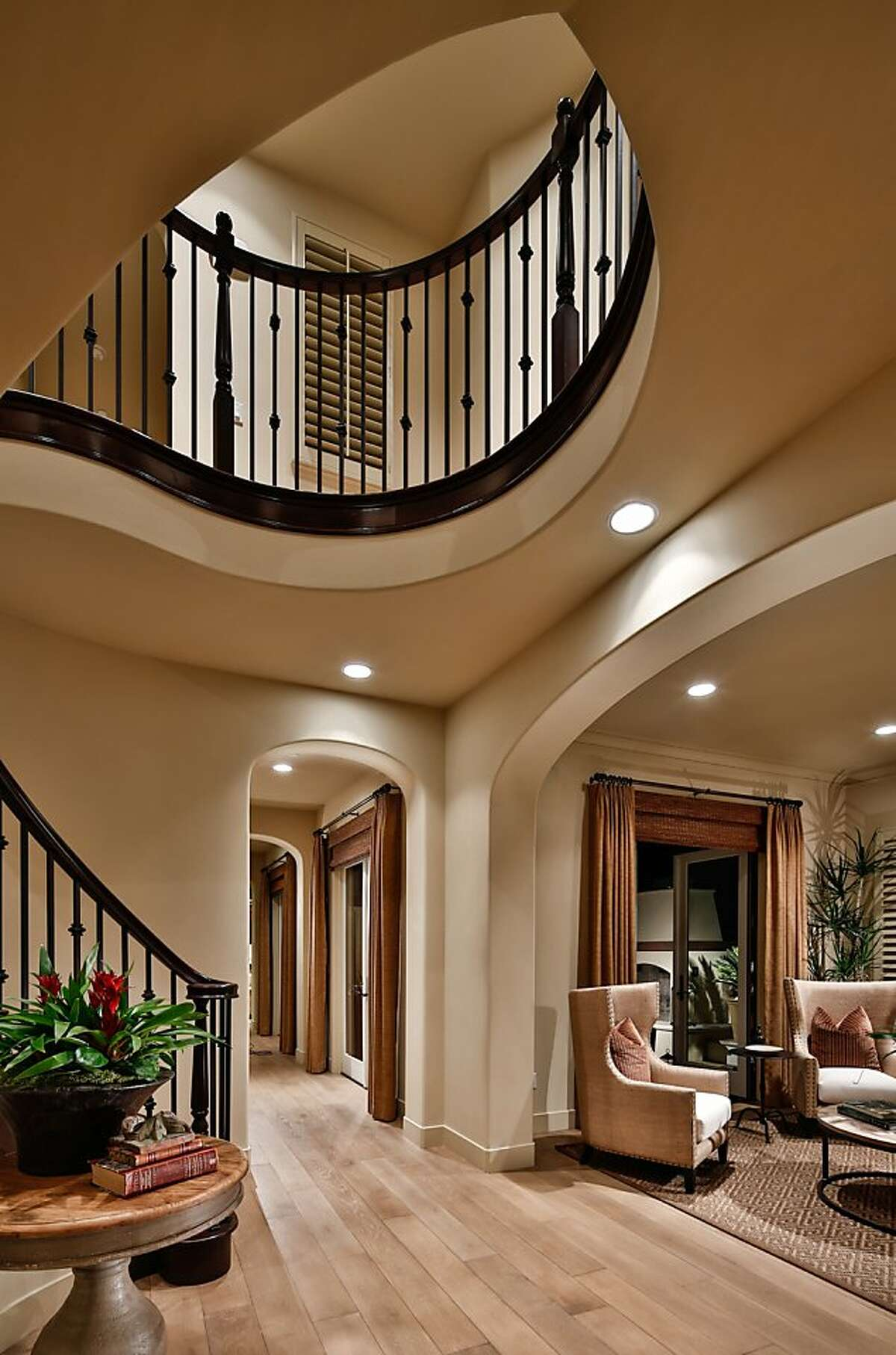 The grand staircase includes a curved bannister.
