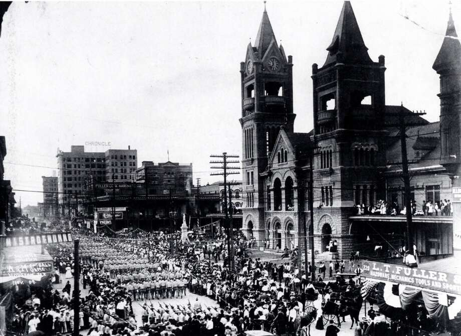 """Houston's fourth City HallCompleted in 1904. In this 1909 photo, Texas A&M cadets march past before a football game. At the building's base was the City Hall Market, where vendors sold produce and fish -- the """"market"""" of downtown's Market Square. In 1939, Houston built a new City Hall (the one that still stands). The brick building  morphed into a bus station, then burned in 1960. credit: Houston Metropolitan Research Center (HMRC) Photo: Houston Metropolitan Research Ce"""