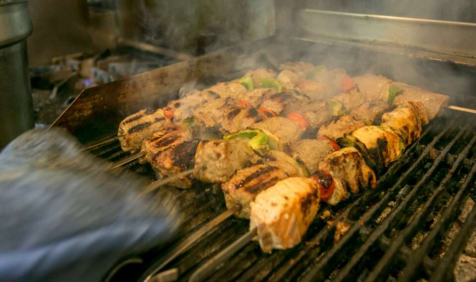 Kabobs cook on the grill at roya afghan cuisine in for Afghan kabob cuisine