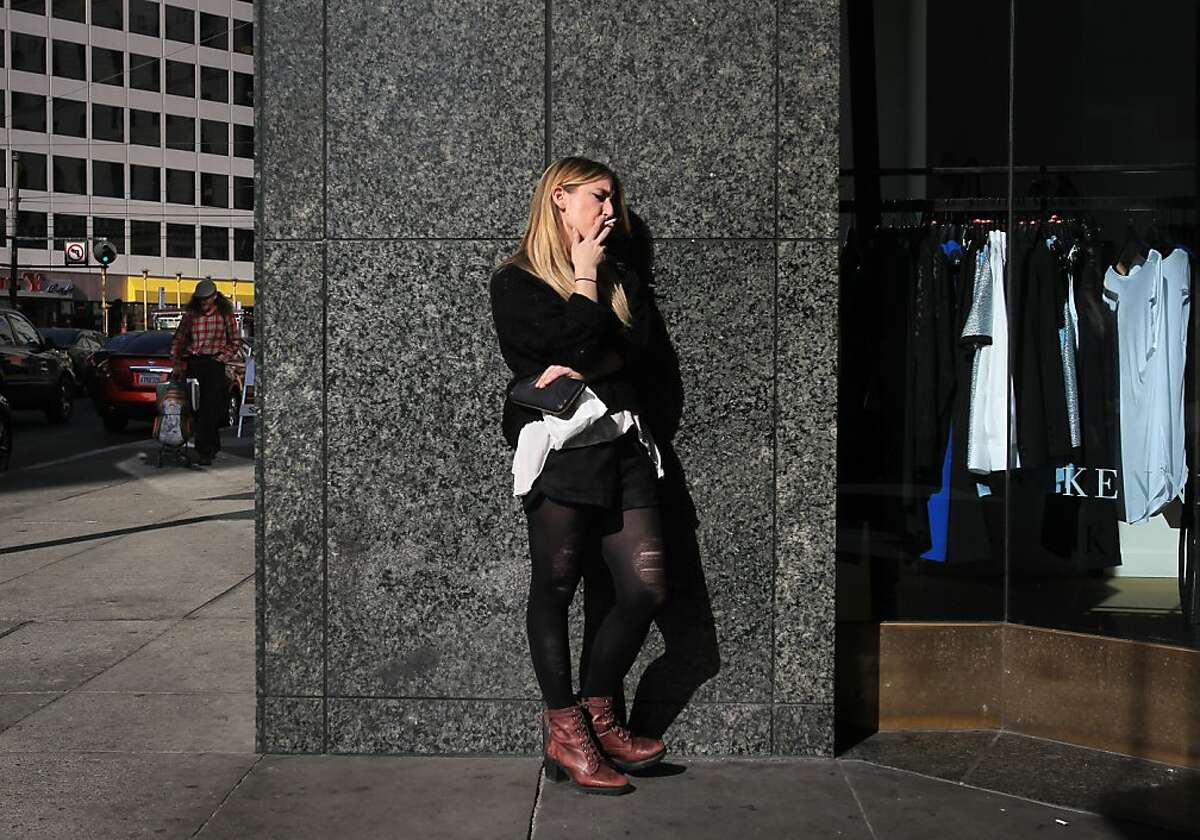 Alexis Bowles, 23, smokes a cigarette during her break from a job in Westfield Mall November 7, 2013 in downtown San Francisco, Calif. Those who wish to increase the tax on cigarettes to pay for cancer research are collecting signatures again after a narrow defeat at the ballot box last year.