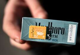 "A ""California Tax Paid"" stamp can be seen on the bottom of a pack of cigarettes bought by Alexis Bowles, 23, November 7, 2013 in downtown San Francisco, Calif. Those who wish to increase the tax on cigarettes to pay for cancer research are collecting signatures again after a narrow defeat at the ballot box last year."