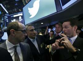 Twitter CEO Dick Costolo, left, and Mike Gupta, center, chief financial officer of Twitter, talk with specialist Glenn Carell during Twitter's IPO, on the floor of the New York Stock Exchange, Thursday, Nov. 7, 2013. If Twitter's bankers and executives were hoping for a surge on the day of the stock's public debut, they got it. The stock opened at $45.10 a share on its first day of trading, 73 percent above its initial offering price.  (AP Photo/Richard Drew)