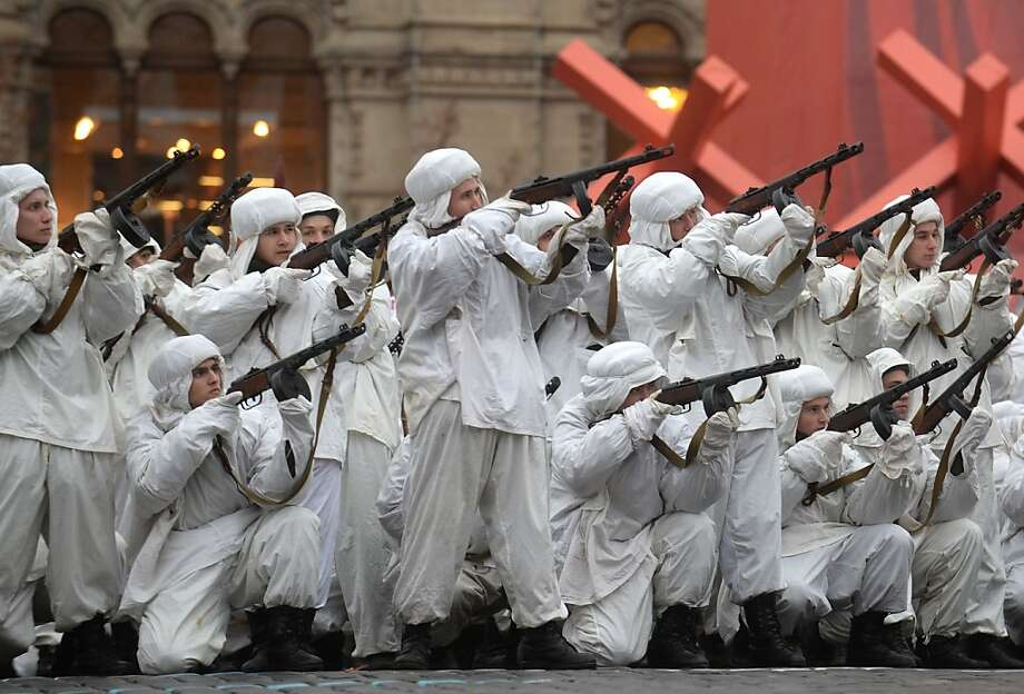 Wearing World War II-era winter camouflage smocks, Russian soldiers pretend to fire their weapons at a 
